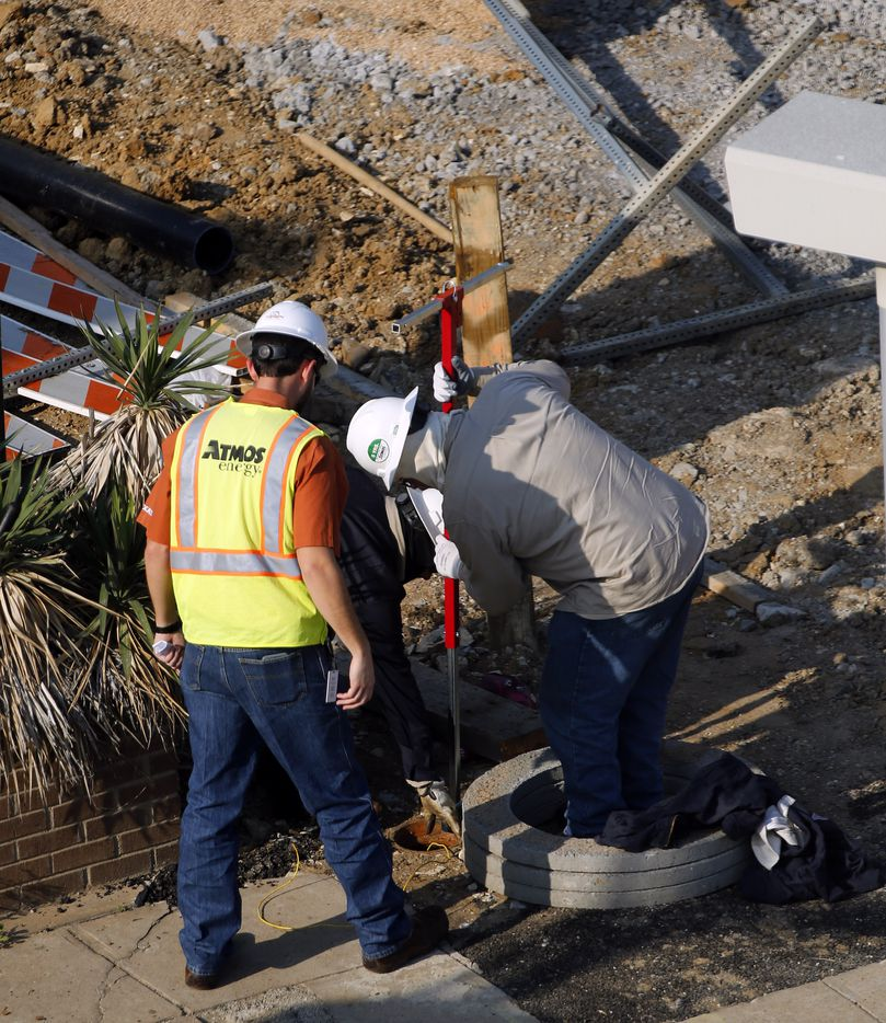 Gas line workers turn off a valve on Commerce St. shortly before the fire was extinguished.