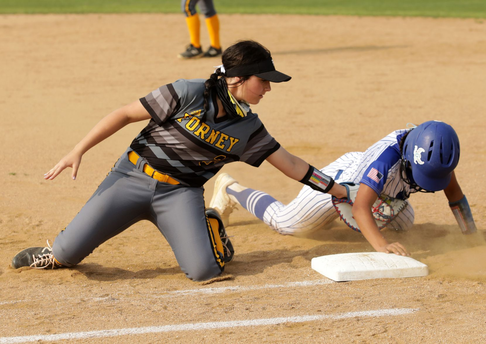 Rylie Harris attempts to stop Hayelie Acosta from returning to first base during a softball game between Forney at North Forney at North Forney High School in Forney, TX, on Apr. 9, 2021. (Jason Janik/Special Contributor)