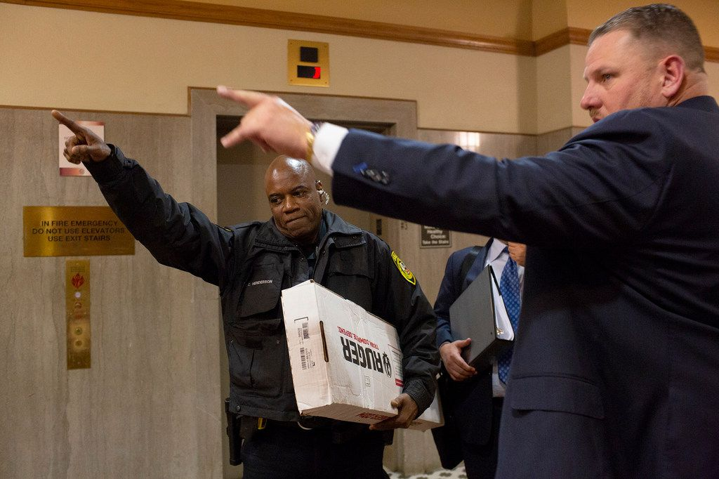 Deputy Terry Henderson carries a Ruger AR-556 model 8500, the same type of rifle used by the gunman to attack First Baptist Church of Sutherland Springs, out of the Bexar County Courthouse for attorney Jason Webster, right, who showed Judge Karen Pozza the rifle during a hearing as Webster agued on behalf of survivors and victims' families who have sued Academy Sports + Outdoors, in San Antonio on Thursday, Jan. 31, 2018. The deputy had to bring the rifle into and out of the building for the hearing.