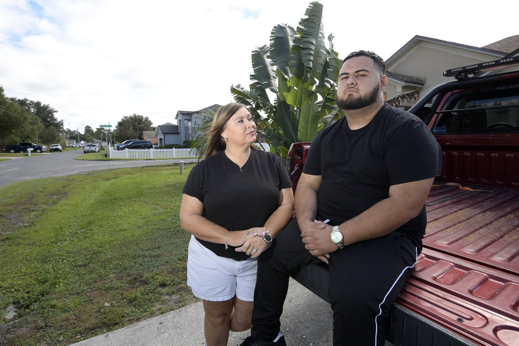 Brandon Gonzales sits on the back of his stepfather's truck with his mother, Pam Lopez, by his side. He hopes he can build a new life for himself in Florida.