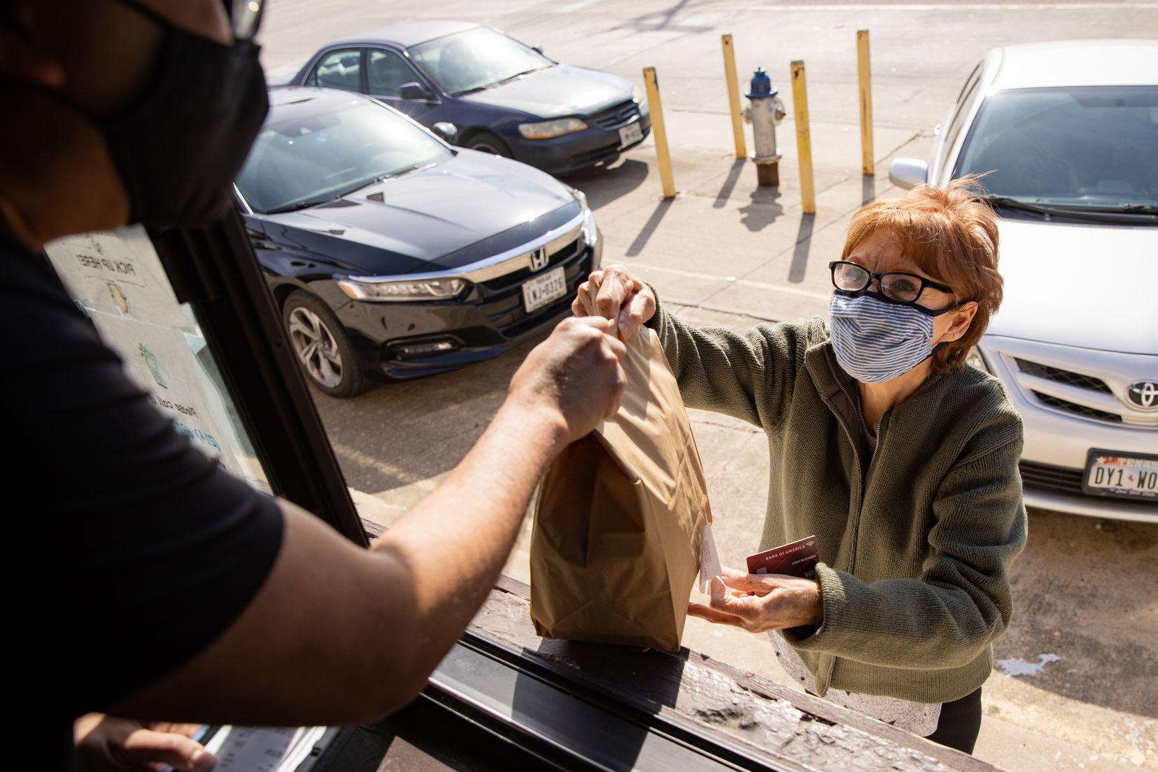 Longtime customer Carol Brown (right) picks up an order at the walk-up window from Joe Pumphuang at Bangkok at Greenville restaurant in Dallas.