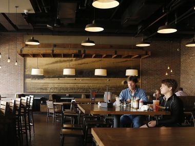 Roman Kikta and son Alex Kikta eat lunch together at Tri Tip Grill at The Star in Frisco in March last year just ahead of an order from Texas Gov. Greg Abbott temporarily closed schools, restaurants, gyms and bars statewide. As a result of the struggles of 2020, Frisco restaurants and bars reported more than $52.6 million in alcohol sales last year, a drop of 23% from 2019.