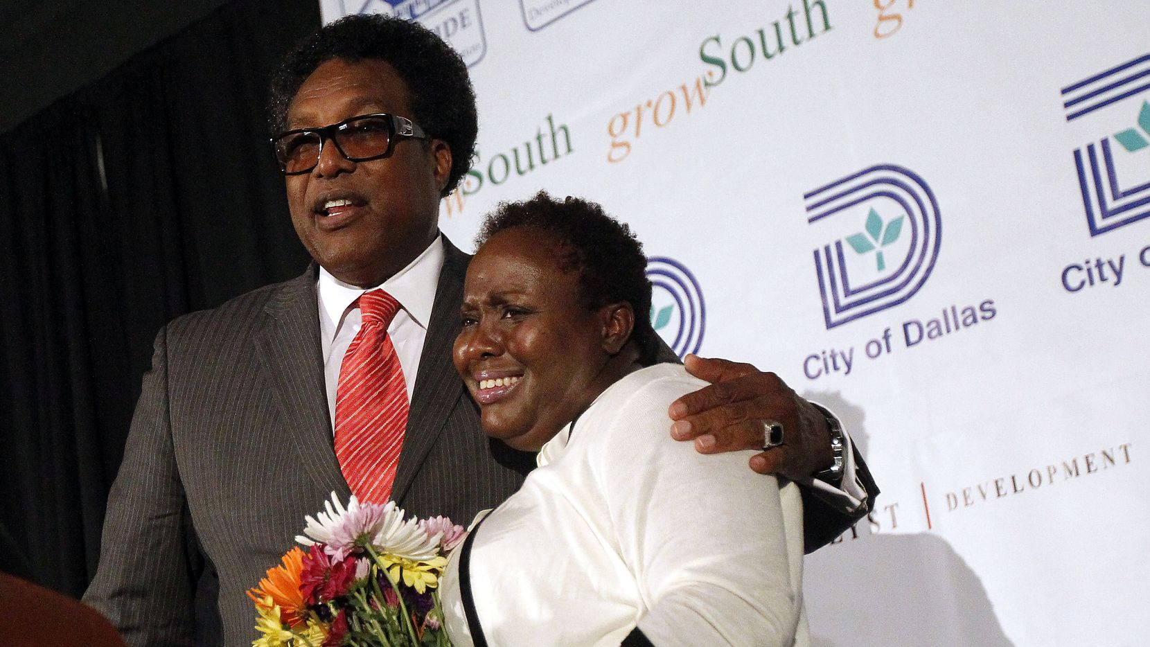 Dwaine Caraway presented a bouquet of flowers to Carolyn Davis at the new Lancaster Urban Village in 2014, when both were Dallas City Council members.