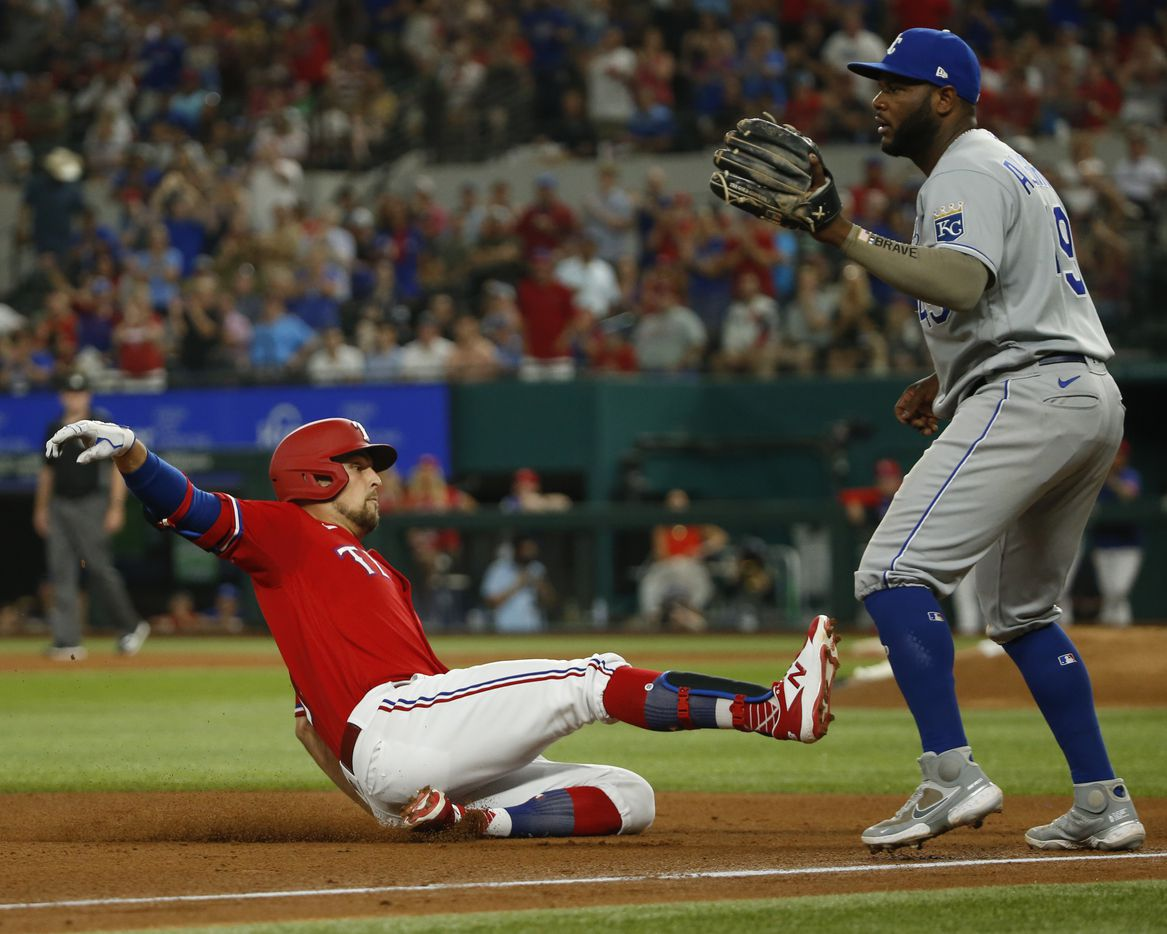 Texas Rangers first baseman Nate Lowe (30) slides into third base ahead of Kansas City Royals third baseman Hanser Alberto (49) after an RBI triple during the fourth inning at Globe Life Field on Friday, June 25, 2021, in Arlington. (Elias Valverde II/The Dallas Morning News)
