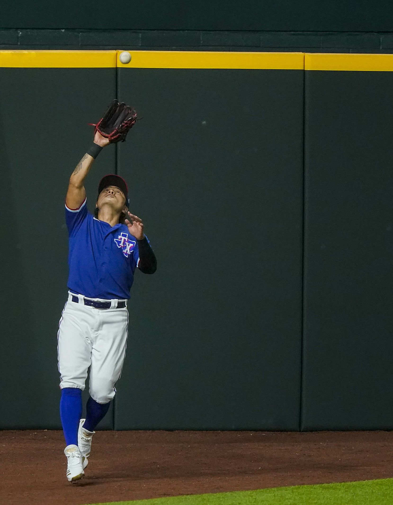 Texas Rangers outfielder Shin-Soo Choo makes a catch on the left field warning track on a fly ball of the bat of the Colorado Rockies Charlie Blackmon during the fifth inning of an exhibition game at Globe Life Field on Tuesday, July 21, 2020.