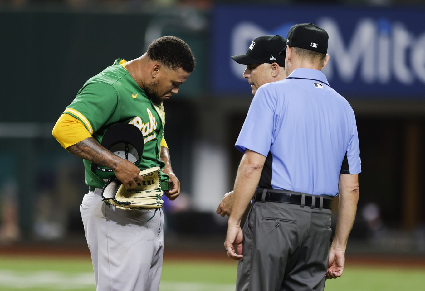 Home plate umpire Dan Iassogna and third base umpire Andy Fletcher inspect Oakland Athletics starting pitcher Frankie Montas' (47) belt, glove and hat after the fifth inning of a baseball game against the Texas Rangers in Arlington, Monday, June 21, 2021. (Brandon Wade/Special Contributor)