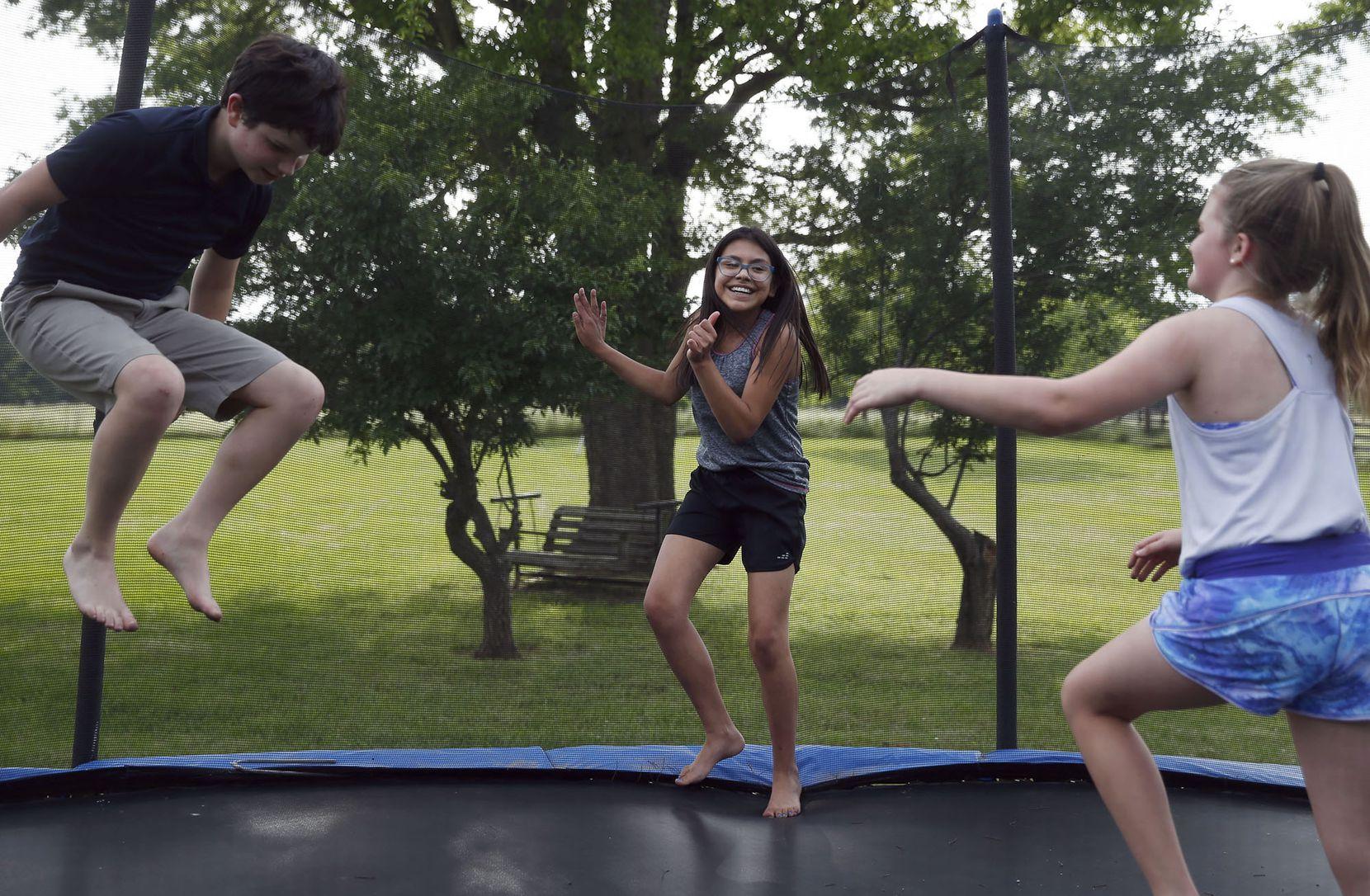 Simon Cooper (izquierda), Emi Ballard, (centro) y Spencer Butrum (derecha) juegan en un trampolín en la casa de Emi en Longview, Texas. (Vernon Bryant/DMN)