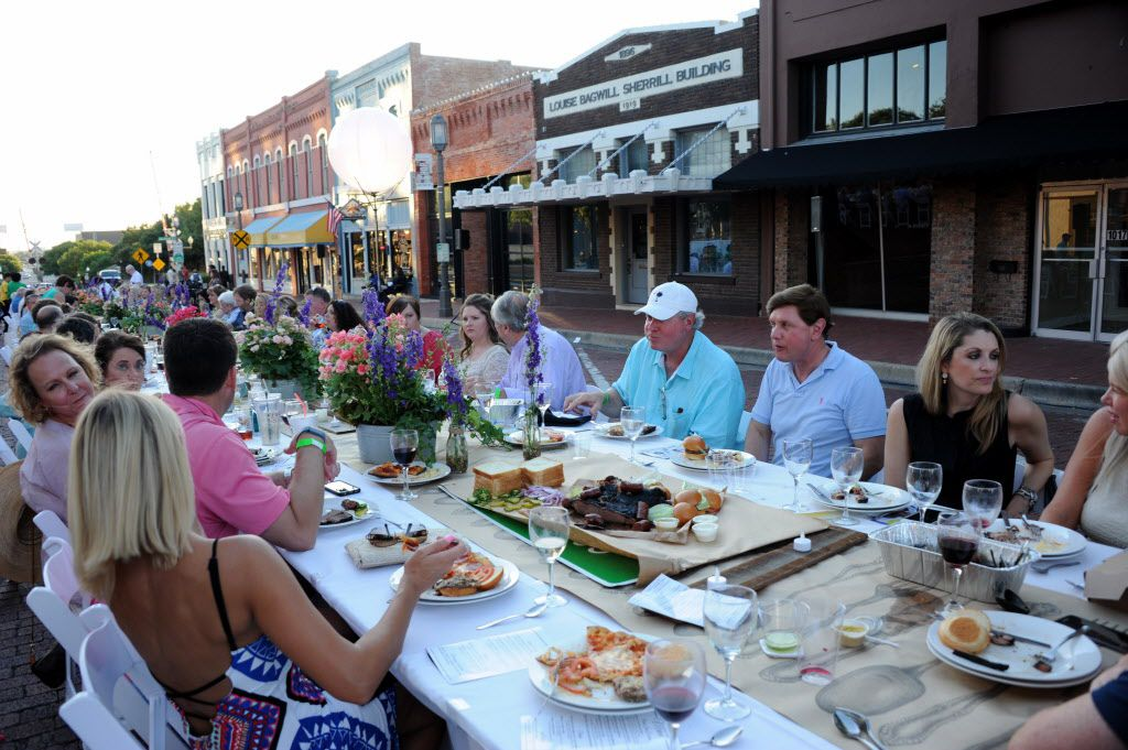 Guests eat and drink at an outdoor table during Night Out on 15th Street in downtown Plano.