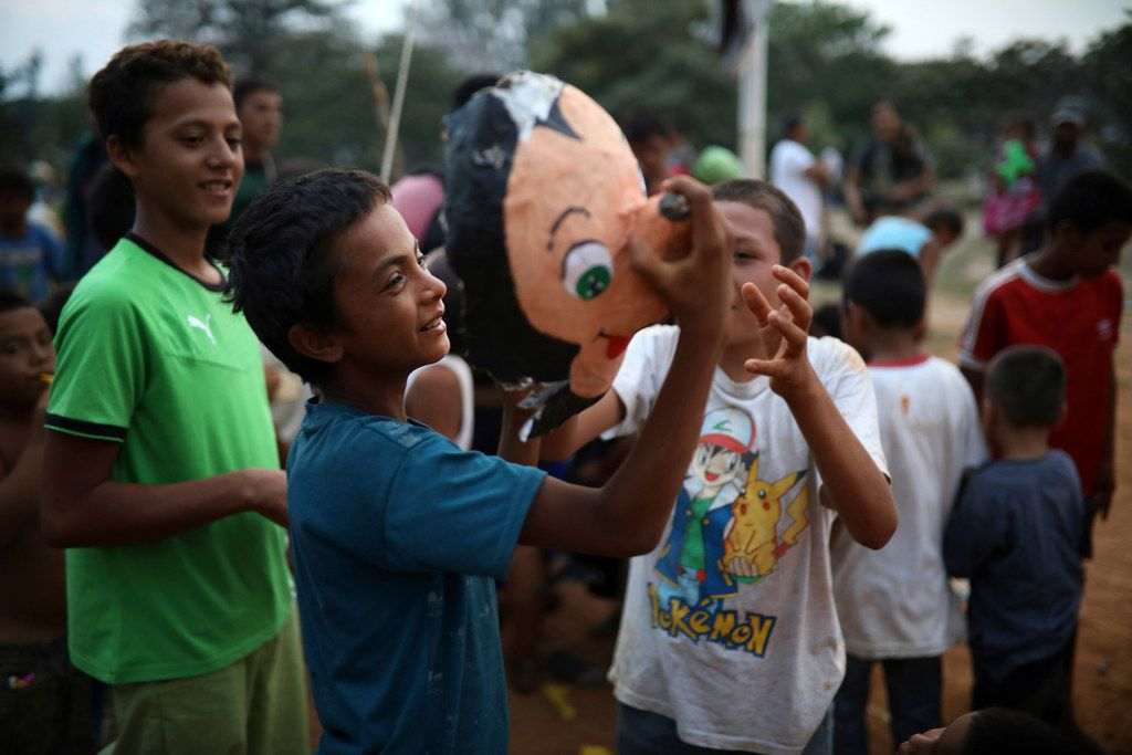 Children play with the face of a Mickey Mouse pinata, at the sports club where Central American migrants traveling with the annual Stations of the Cross caravan have been camped out in Matias Romero, Oaxaca State, Mexico, Wednesday, April 4, 2018. The Mexican government began handing out transit or humanitarian visas to people in a caravan of Central American migrants, and said the procession of 1,000 or so migrants that drew criticism from President Donald Trump had begun to disperse.