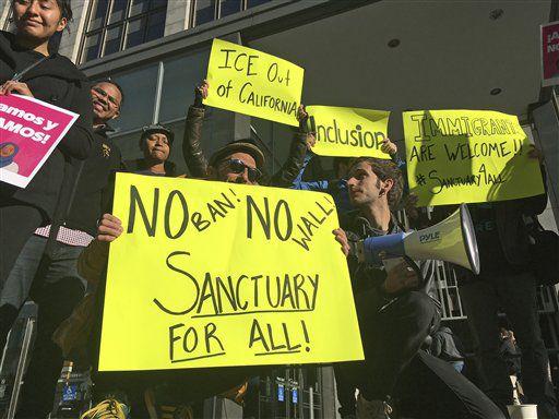 Manifestantes sostienen letreros a las afueras de una corte en la que un juez federal escuchará argumentos en la primera demanda que disputa el decreto del presidente Donald Trump para retener fondos a las comunidades que limiten su cooperación con las autoridades . Foto AP