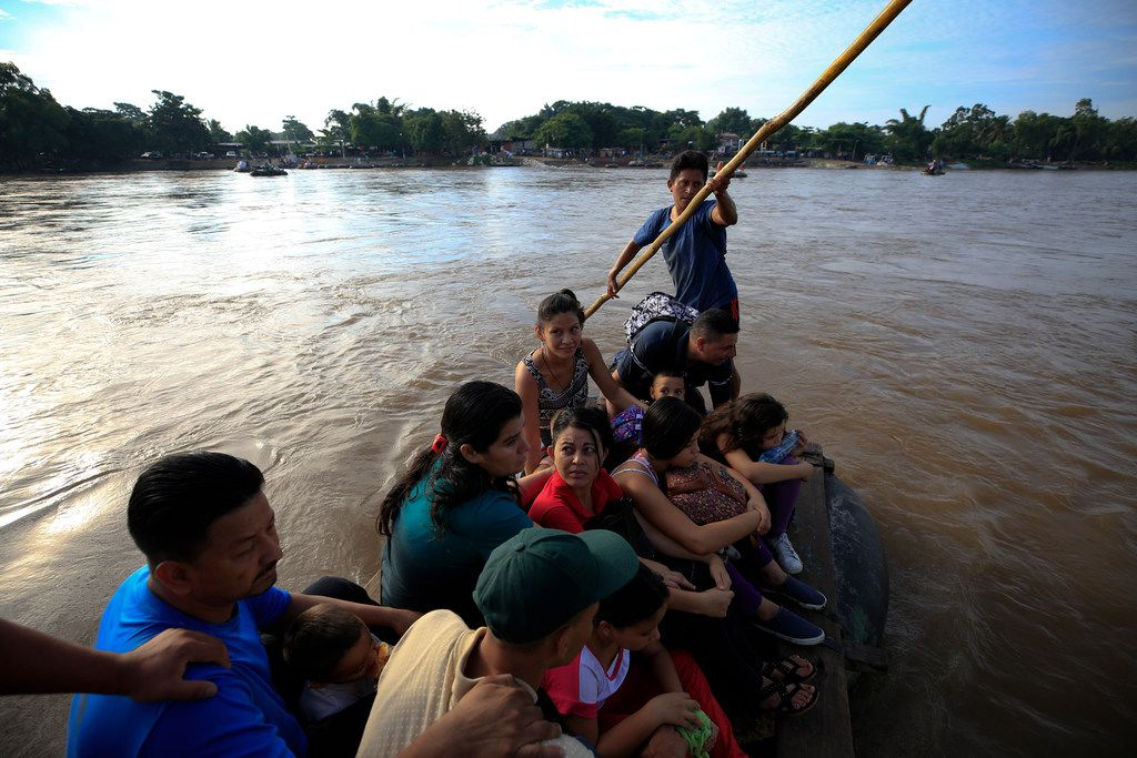 A group of more than a dozen Honduran migrants ride a raft across the Suchiate river after between Tecun Uman, Guatemala, top, and Ciudad Hidalgo, Mexico, Friday, June 14, 2019. Raftsmen and riverfront business operators said the flow of migrants through the crossing has slowed since the announcement a few days ago that Mexico's new National Guard would be deploying to the border.
