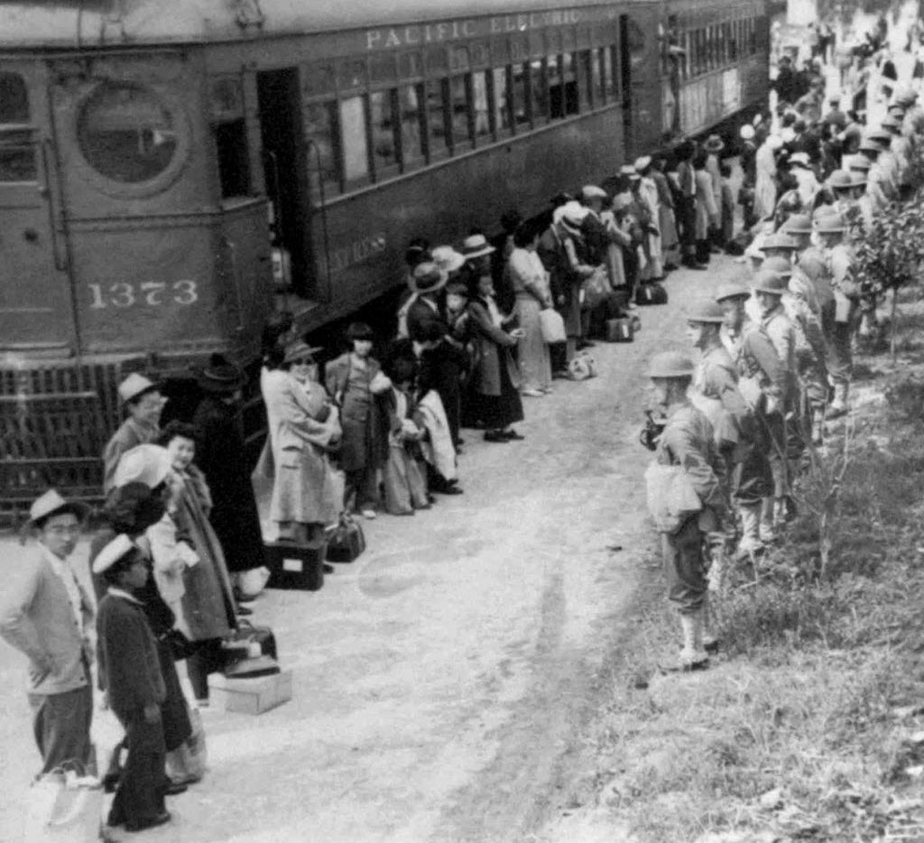 In an undated handout photo from the National Archives, people of Japanese descent line up for a train that will take them to an internment camp at Gila River, Ariz. from the Santa Anita assembly camp in Arcadia, Calif., in 1942.
