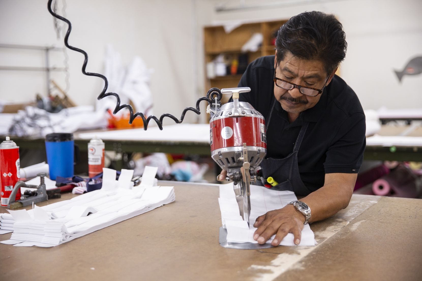 Business owner Rudy Romero cuts fabric at T&Q Cutting Services on May 2, 2020, in Dallas. Romero has been helping supply hospitals and others with PPE such as face masks and gowns.
