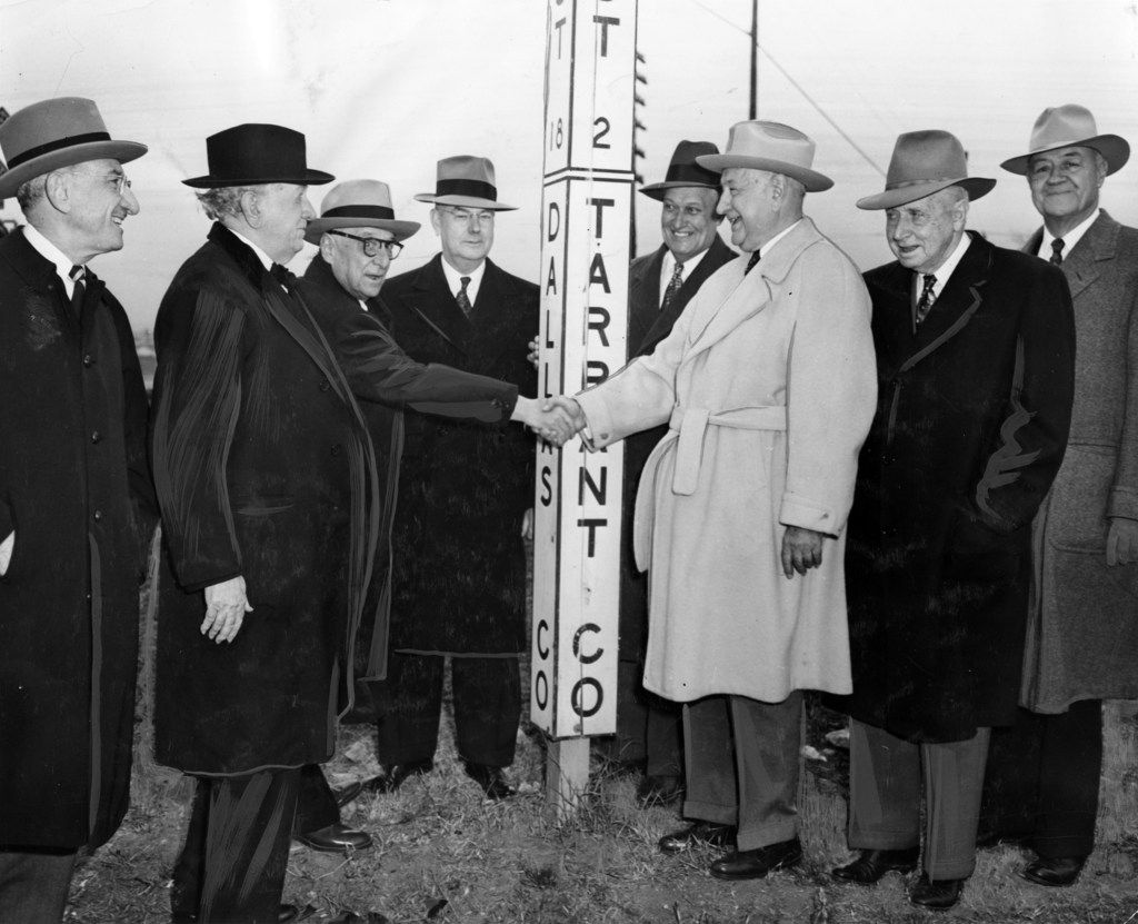 Dallas Times-Herald publisher Tom C. Gooch reaches across the county line to welcome Amon G. Carter to East Texas and present him with a passport to Dallas County for 1952. Looking on are, left to right, Fred Florence, president of Republic National Bank of Dallas, Sen. Tom Connally, Secretary of the Treasury John W. Snyder, Dallas Mayor J, B. Adoue Jr., Nathan Adams, honorary chairman of the board of First National Bank of Dallas and W.B. Clayton, General Electric Company vice president. Gooch and his party were on hand to greet 30 buses carrying 1,000 football fans to the Cotton Bowl.