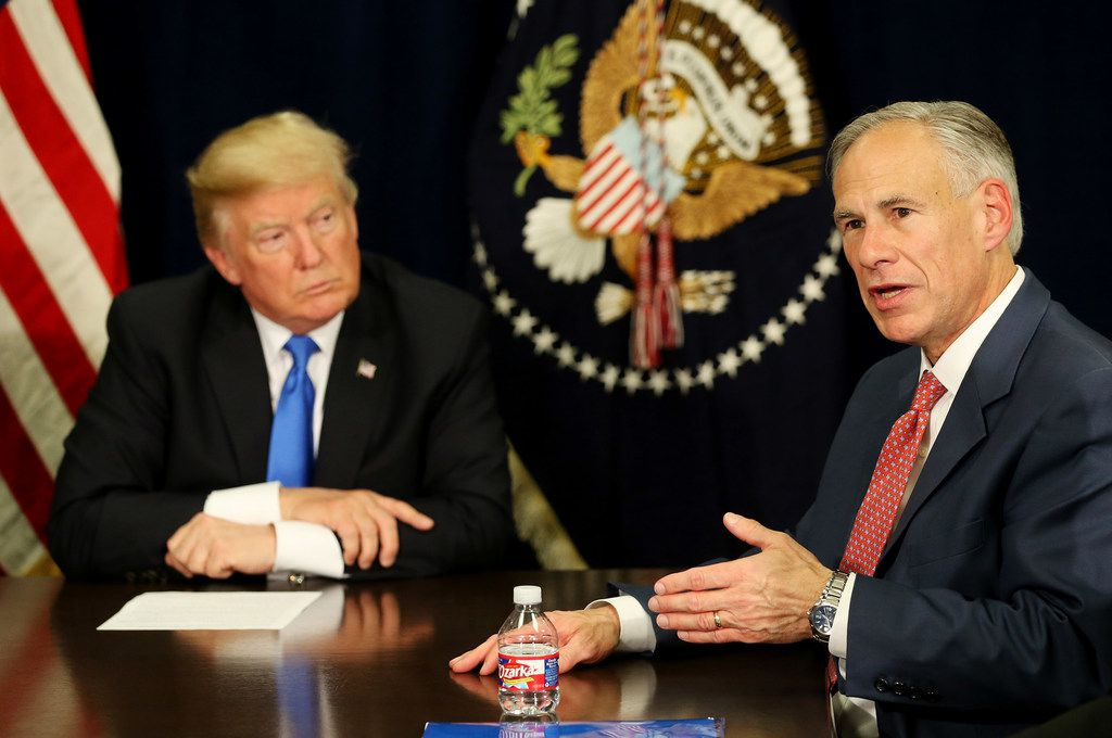 Texas Gov. Greg Abbott speaks while President Donald Trump watches on they discuss hurricane response at Signature Flight Support near Love Field in Dallas on Oct. 25, 2017.