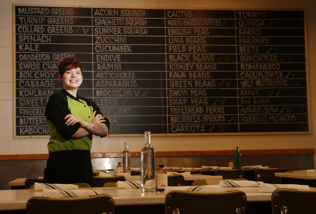 Executive chef Suki Otsuki in front of a board listing the fresh produce du jour at Mudhen Meat and Greens