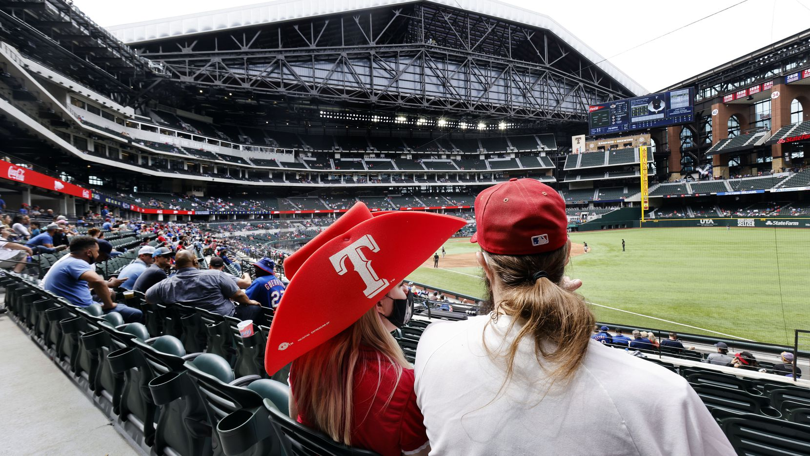 Texas Rangers fans take in an afternoon exhibition baseball game at Globe Life Field in Arlington, Texas. The Rangers were playing the Milwaukee Brewers, Tuesday, March 30, 2021.
