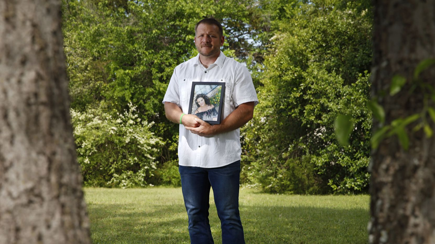 John Palmer poses for a portrait as he holds up a photo of his wife Katie Palmer in the front yard of their home in Denison on May 1.. John lost his wife Katie Palmer to a car accident in April. Katie's organs were donated and helped seven people.