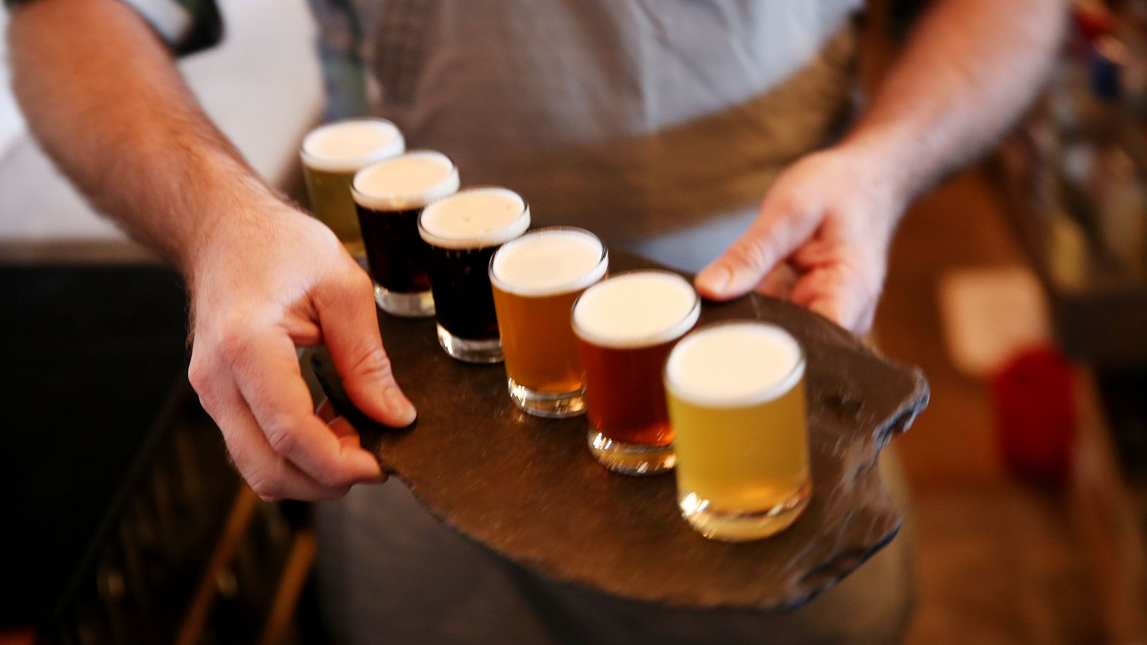 Joshua Dawn, co-owner of Small Brewpub, delivers a flight of beer to patrons inside the Oak Cliff restaurant. Get there before it closes in December 2019.
