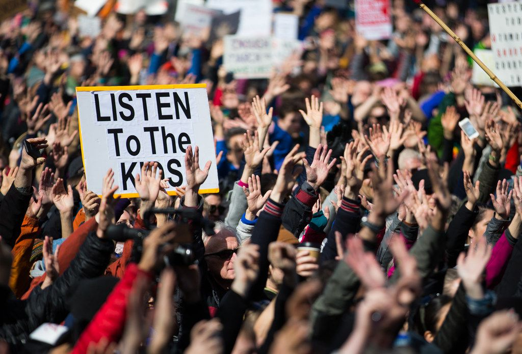 People hold their hands up as directed by musician Brandi Carlile at Seattle Center during the March for Our Lives rally March 24 in Seattle.