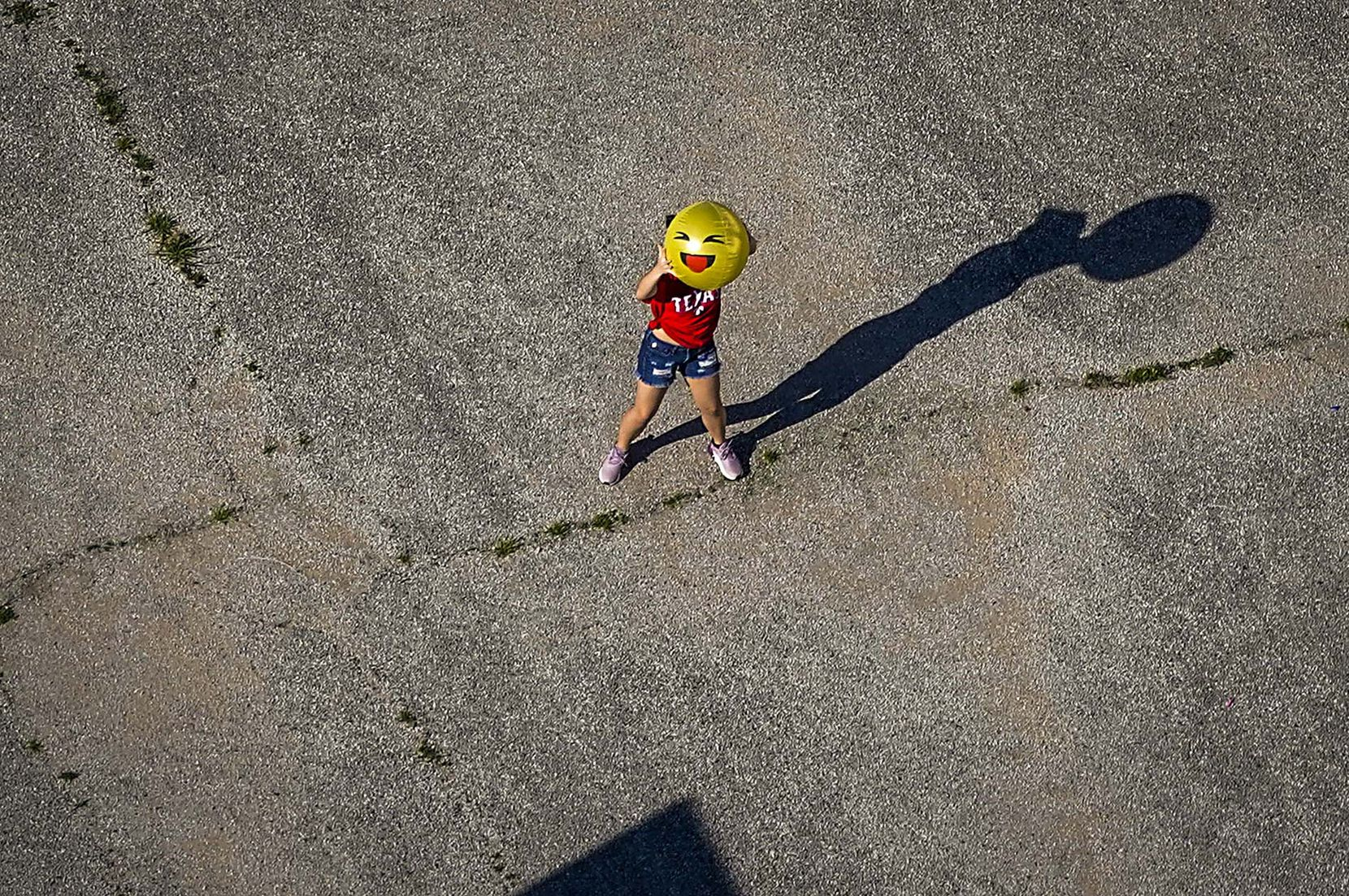 A child holds up a smiley face ball on a playground at D.A. Hulcy Middle School on Tuesday, March 24, 2020 in Dallas.