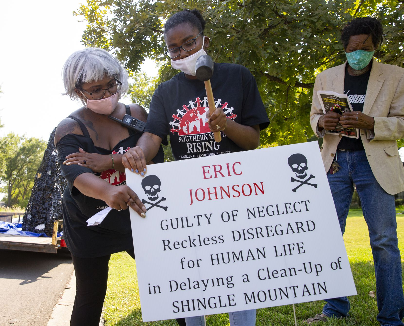 Oquinn (left) and demonstrator Essence Telteh place a sign near the home of Dallas Mayor Eric Johnson, who also was on activists' list of targets for criticism Saturday.