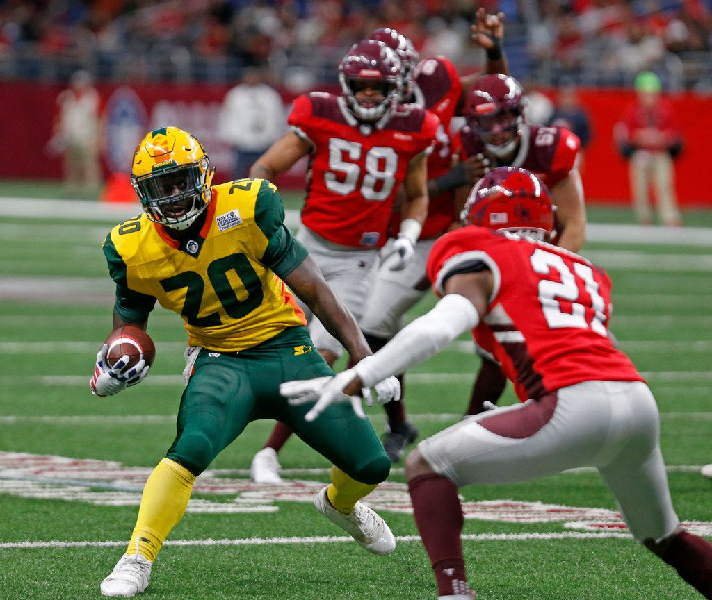 Tim Cook (20) of the Arizona Hotshots runs around Duke Thomas (21) of the San Antonio Commanders to score a touchdown during an Alliance of American Football game at the Alamodome last month. The league ceased operations earlier this month and filed for bankruptcy protection Wednesday.