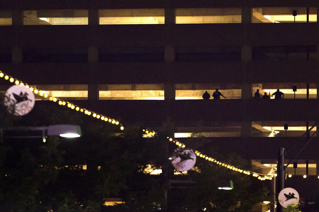 Silhouettes of law enforcement officers are seen in a parking garage in downtown Dallas in the early morning hours of Friday, July 8, 2016. Smiley N. Pool/Staff Photographer