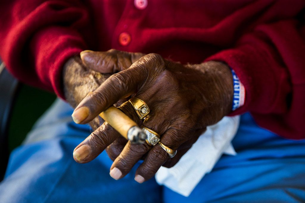 Richard Overton holds a cigar while sitting on his front porch.