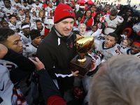 Cedar Hill coach Joey McGuire accepts the Class 5A Division II state semifinal trophy after defeating Lake Travis in 2013. Cedar Hill won the first of back-to-back state titles that year.