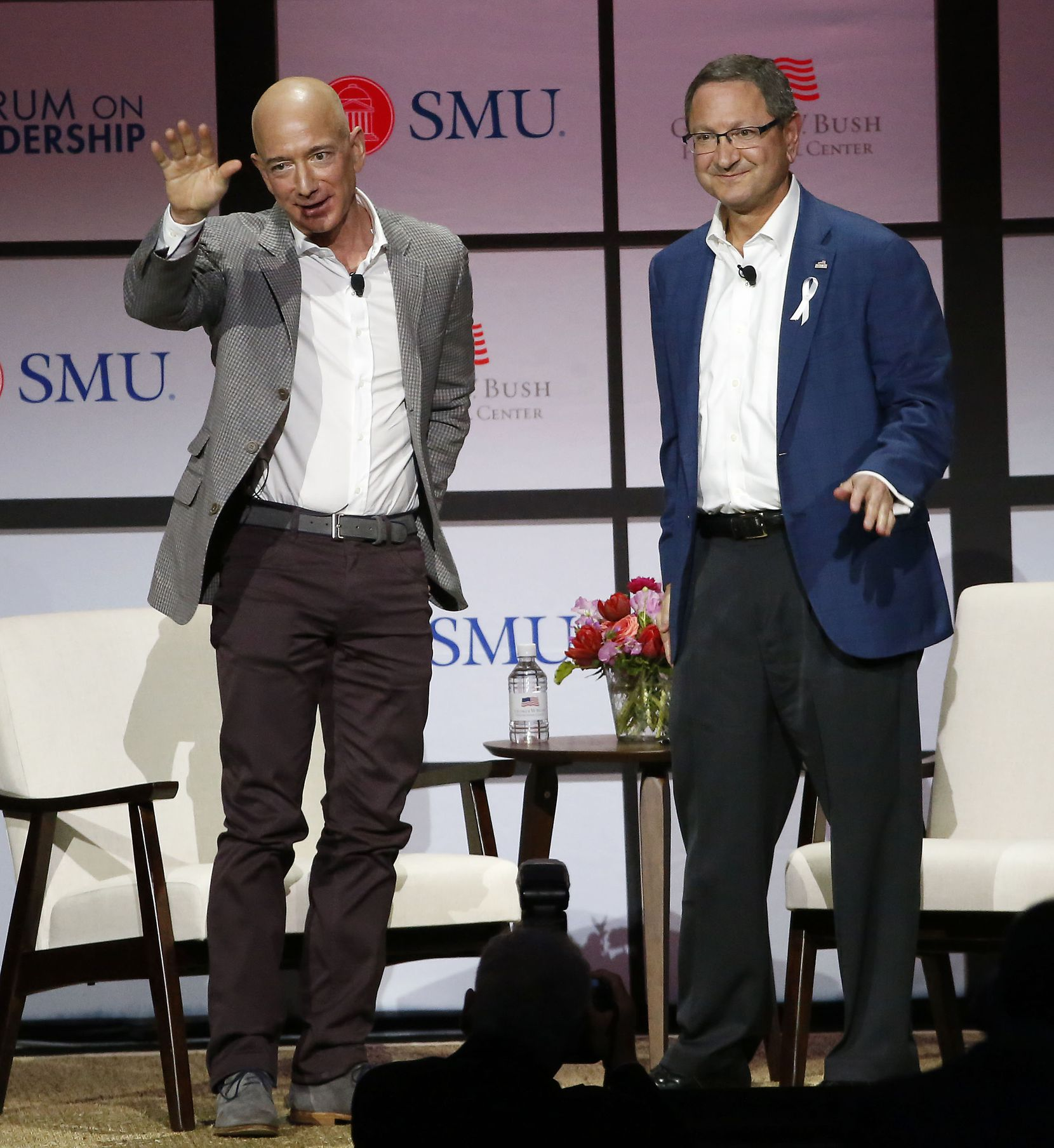 Jeff Bezos, chairman and CEO of Amazon, waved to the crowd next to Ken Hersh, president and chief executive of the George W. Bush Presidential Center, at the 2018 George W. Bush Presidential Center's Forum on Leadership at Moody Coliseum.