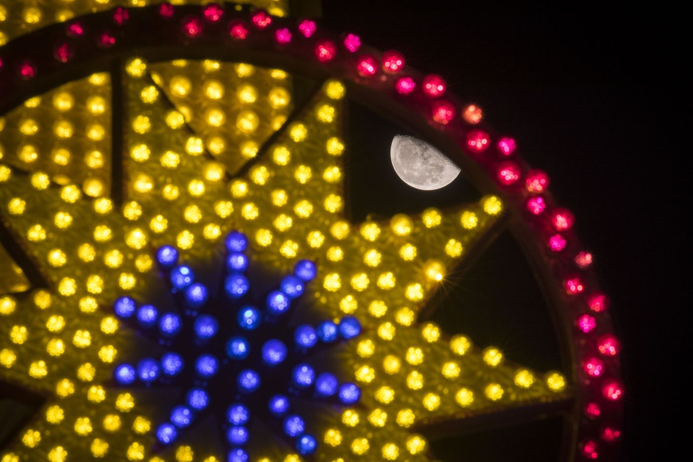 The moon rises behind rides on the Midway at the State Fair of Texas in the early morning hours of Oct. 11.