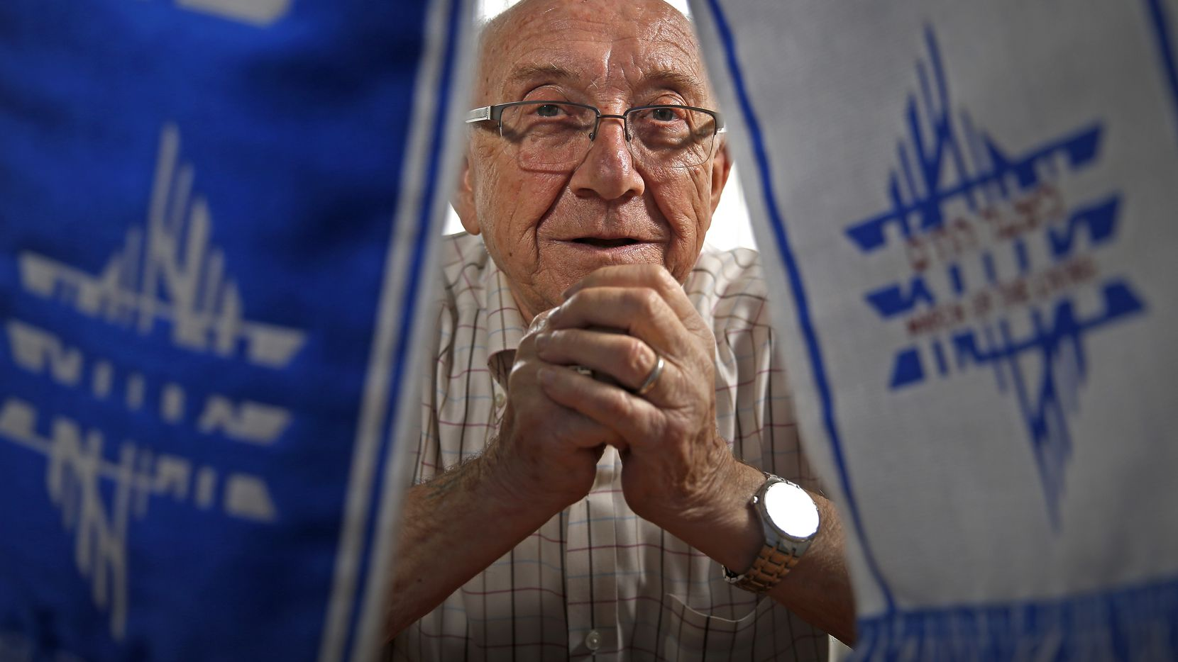 "Max Glauben, a Holocaust survivor, poses for photograph with a ""March of the Living"" scarf at his home in Dallas, in August 2017."