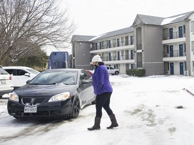 Jammie McGee walks back to her car after finding out the Motel 6 in North Arlington she reserved a room from doesn't have power. McGee said her Westmoreland Road apartment in Dallas lost electricity and water.