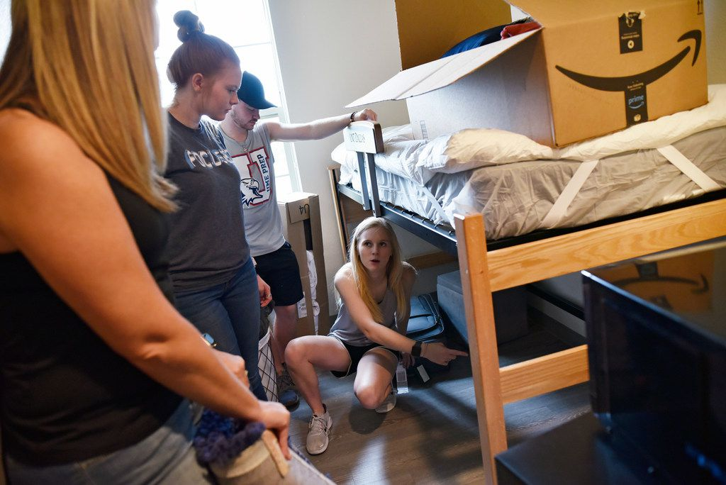 Freshman Makinley Eddlemon (right), 18,  coordinates move in and storage in her dorm room with the help of family and friends.