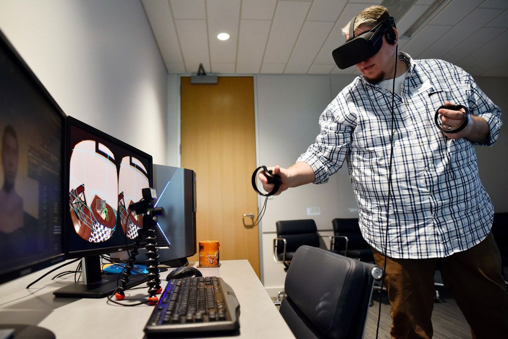Aaron Tate, lead artist for the Brain Performance Institute, demonstrates how the virtual world computer program Charisma works. The eye-piece and hand controllers can help with physically moving items in a virtual world.