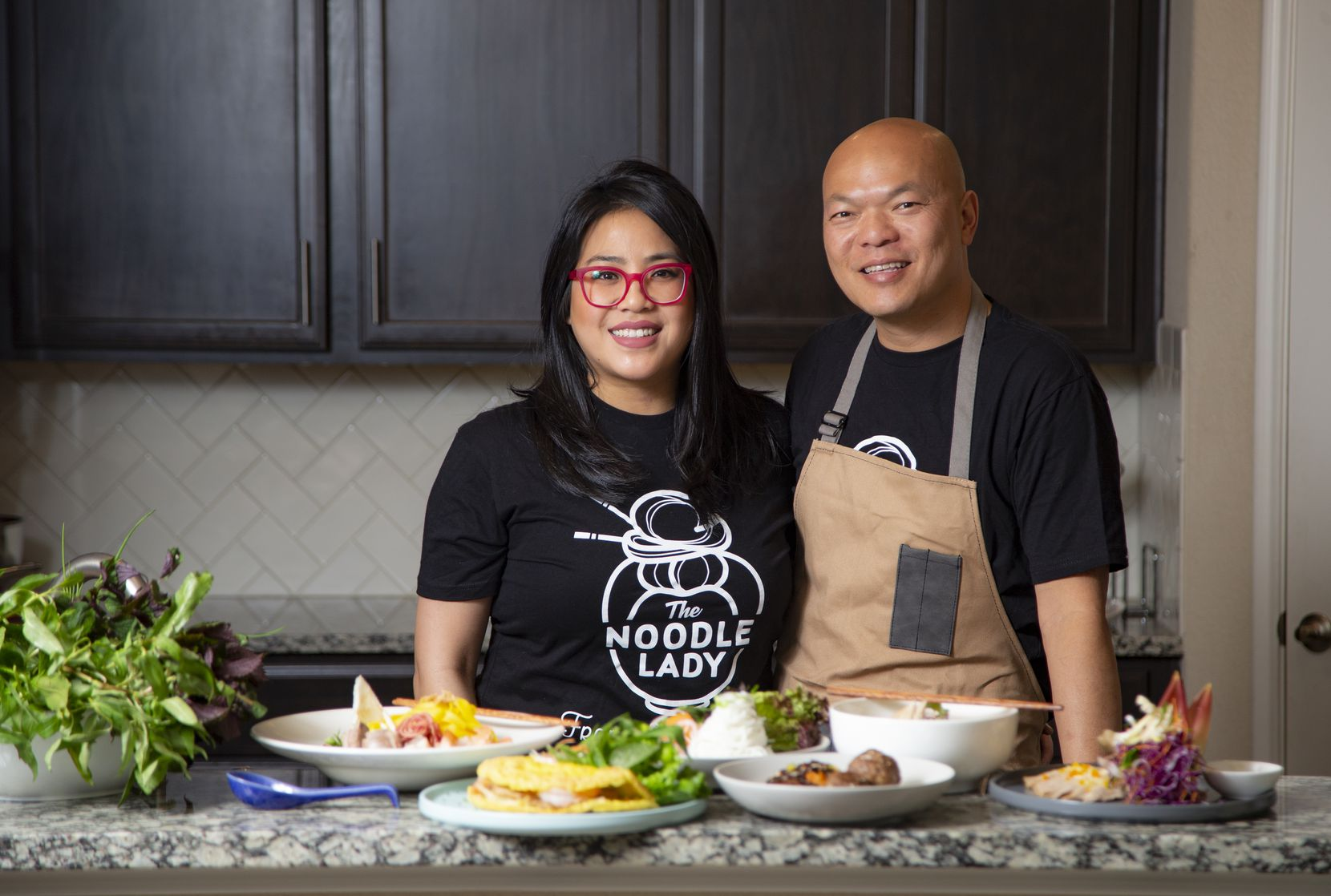 Jennifer Ong-Sikhattana (The Noodle Lady) and her husband, John, pose for a photo in their kitchen in McKinney.