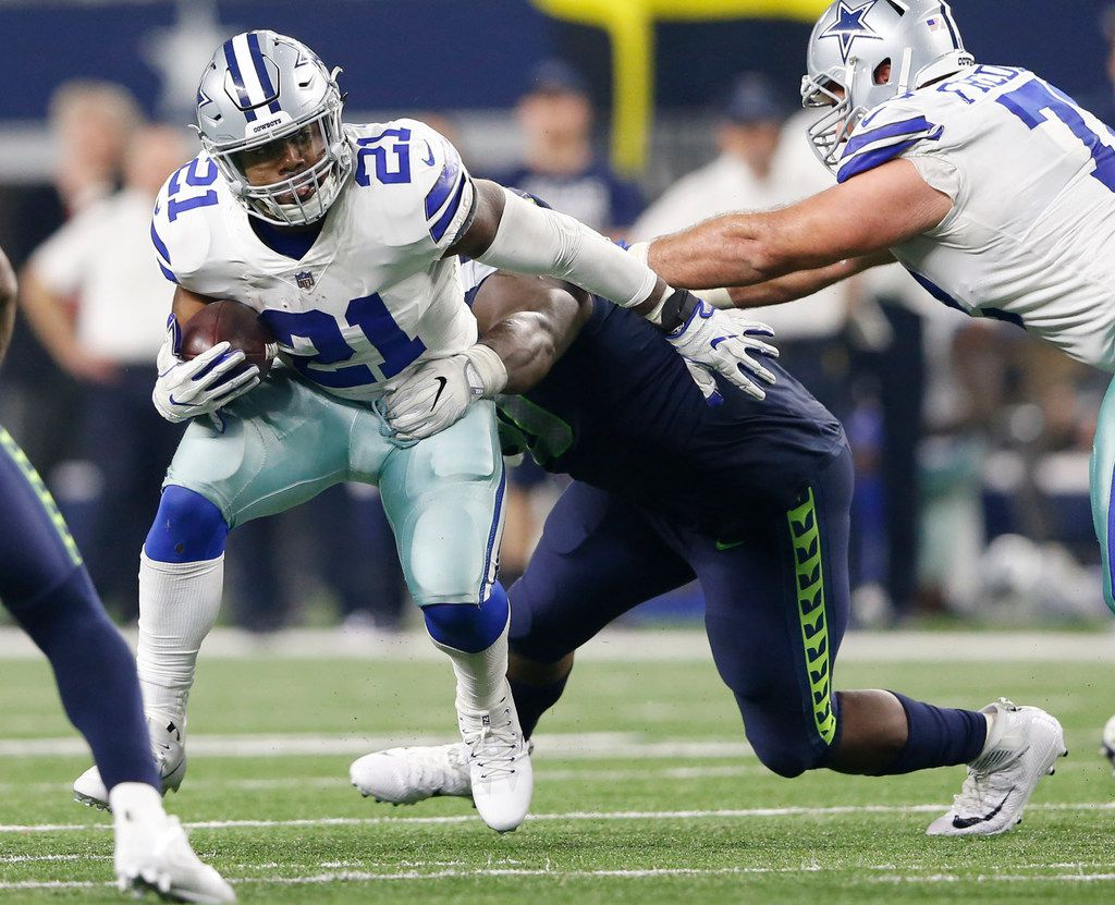 Dallas Cowboys running back Ezekiel Elliott (21) rushes up the field as he is grabbed by Seattle Seahawks defensive tackle Jarran Reed (90) during the second half of play at AT&T Stadium in Arlington, Texas on Sunday, December 24, 2017. Dallas Cowboys lost to the Seattle Seahawks 21-12. (Vernon Bryant/The Dallas Morning News)