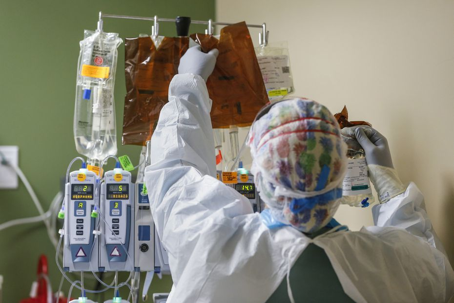 A health care worker changes out an intravenous drip while treating an intubated patient in the Parkland Hospital COVID-19 Tactical Care Unit.