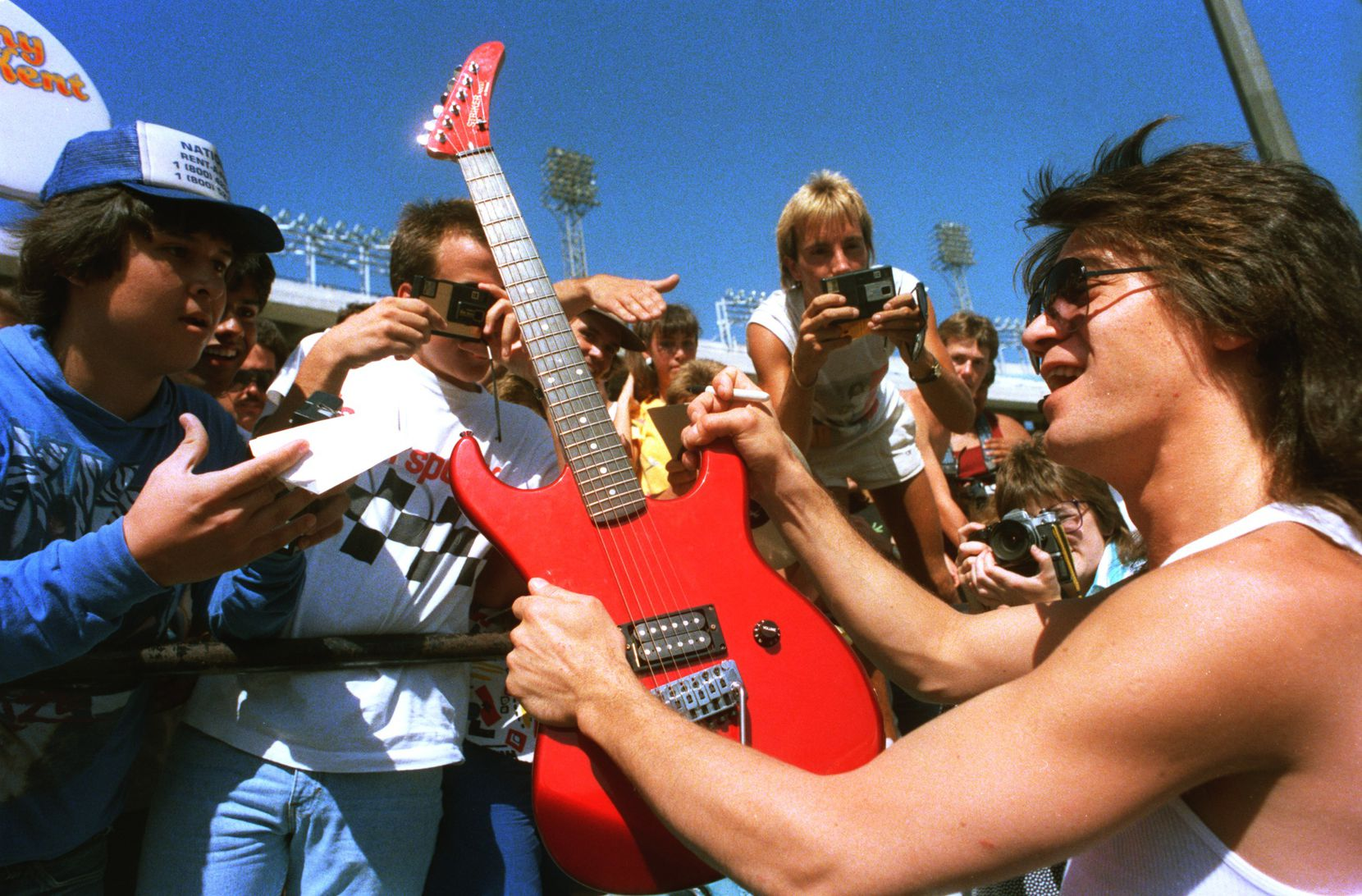 Eddie Van Halen is surrounded by fans at a news conference at the Cotton Bowl on July 17, 1986 ahead of a Texxas Jam concert.