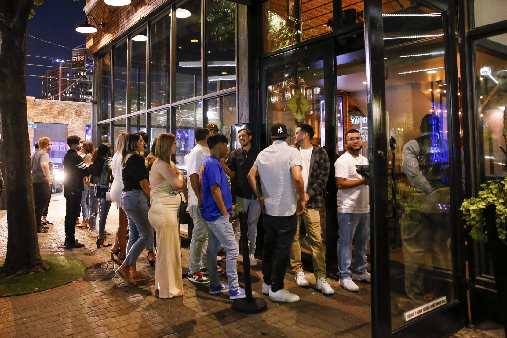 People wait outside to enter Stirr, a bar and restaurant on Main Street in in Deep Ellum.
