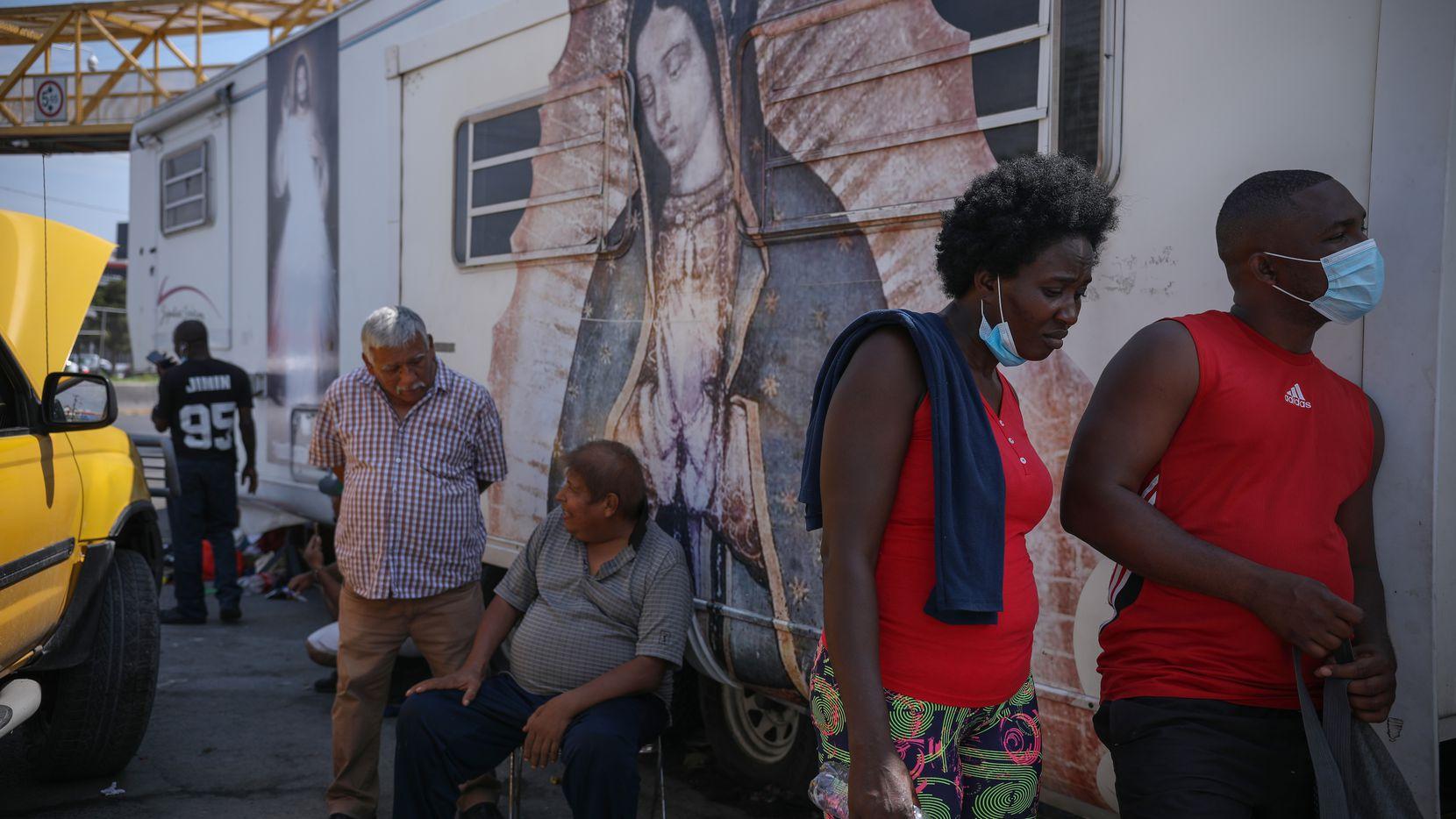 Esther Pierre Louie y su amigo John esperan frente a un mural de la Virgen de Guadalupe el martes 28 de septiembre en Monterrey, México.