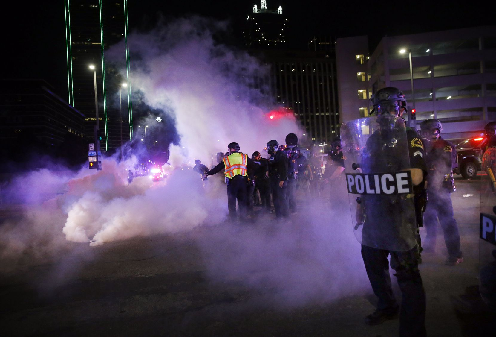 Dallas Police tactical officers fire rounds of tear gas at protestors at Young St. and S. Griffin St. in downtown Dallas, Friday, May 29.