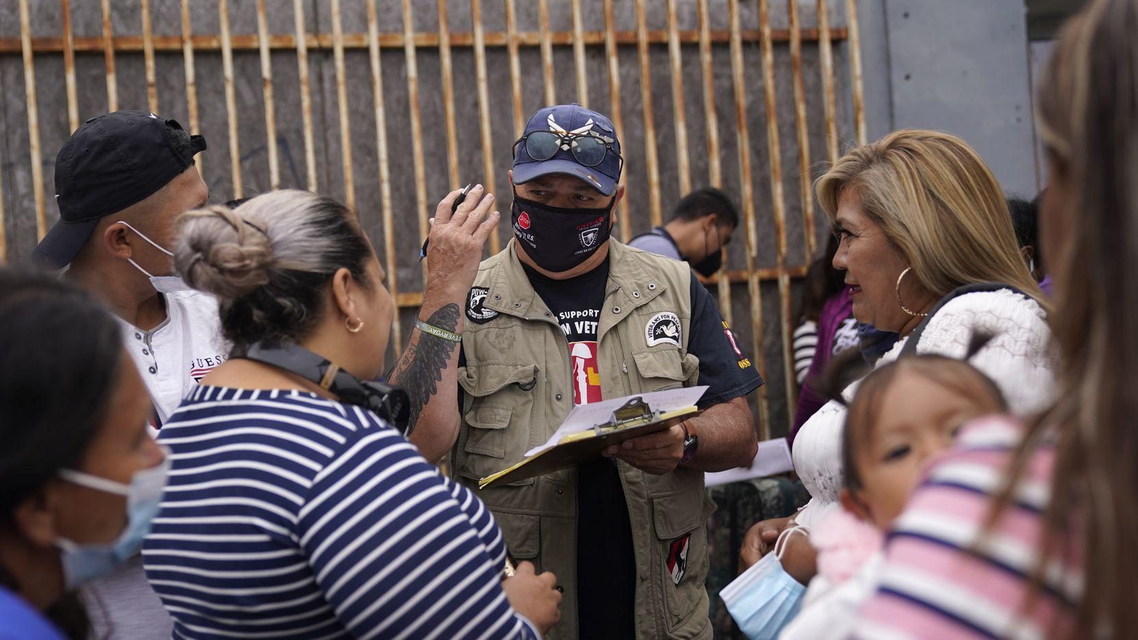El activista Robert Vivar (centro) habla en Tijuana (México) con migrantes que esperan cruzar la frontera para solicitar asilo en Estados Unidos el 5 de julio del 2021.