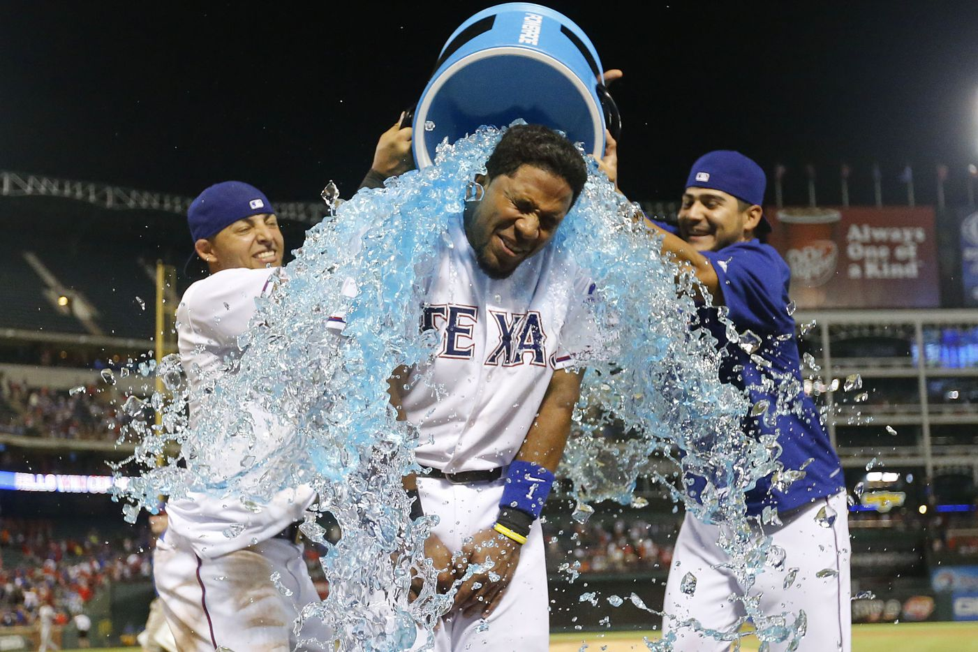 Texas Rangers shortstop Elvis Andrus (1) gets an ice-bath from Texas Rangers second baseman Rougned Odor (12, left) and Texas Rangers starting pitcher Martin Perez (33, right) after the Rangers defeated the Giants 6-3 at Globe Life Ballpark in Arlington, Texas on Friday, July, 31, 2015. (Michael Reaves/The Dallas Morning News) 08082015xPUB