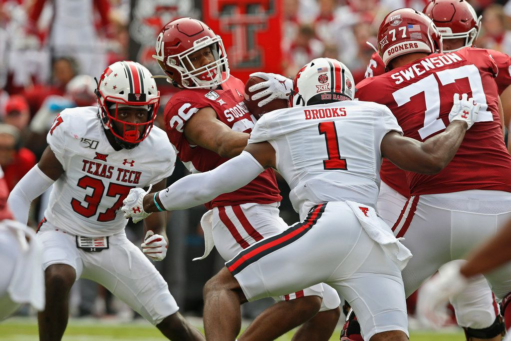 Oklahoma running back Kennedy Brooks (26) is defended by Texas Tech linebacker Xavier Benson (37) and linebacker Jordyn Brooks (1) in the first quarter of an NCAA college football game in Norman, Okla., Saturday, Sept. 28, 2019.