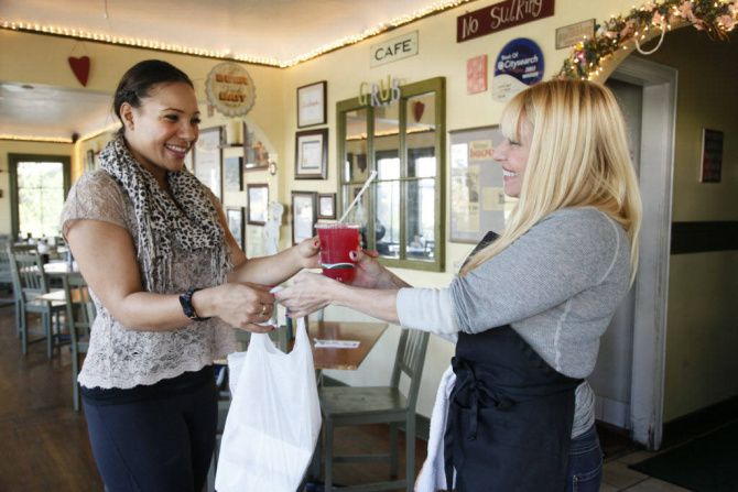 Betty Fraser (right), the owner of Los Angeles restaurant Grub, delivers an online order to customer Chantel Mines. Grub employs the services of online food ordering company GrubHub, which takes about 15% of each order.