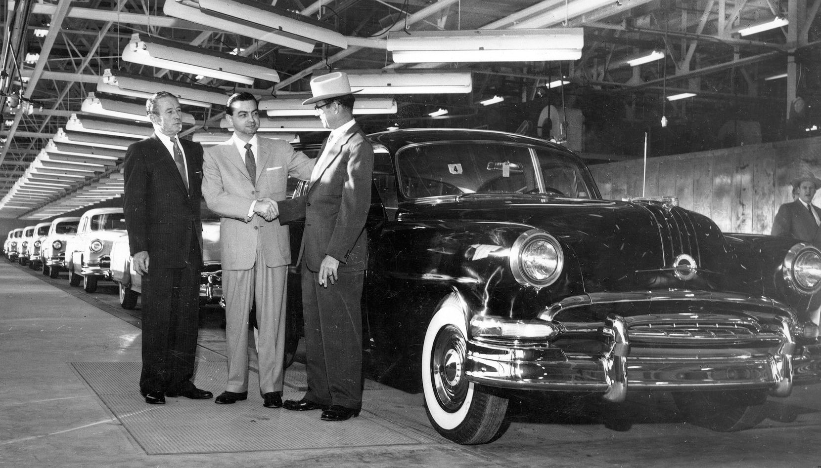 Tom Vandergriff (center), mayor of Arlington, with J.L. Conlon of General Motors and E.C. Klotzburger, General Motors plant manager, with first car off assembly line at General Motors Arlington plant, 01/06/1954.