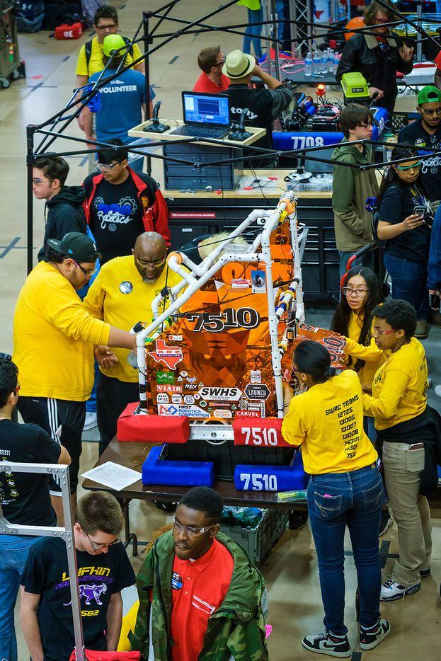 Don Prier (center, left)) works with his Spring Woods High School robotics team in the pits during the FIRST Robotics Competition on Friday, March 22, 2019, in Greenville, Texas.