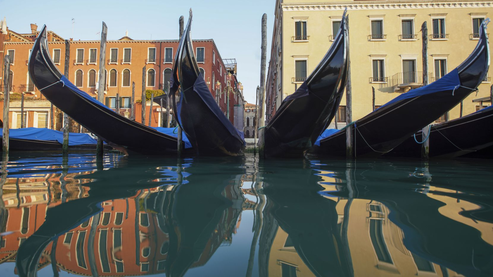 Moored gondolas are reflected on the water of the Gran Canal in Venice, during stay-at-home orders from the Italian government.